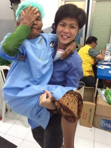 Siew Yian carrying a patient to the surgery waiting room