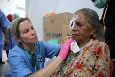 A New Vision volunteer helping a patient